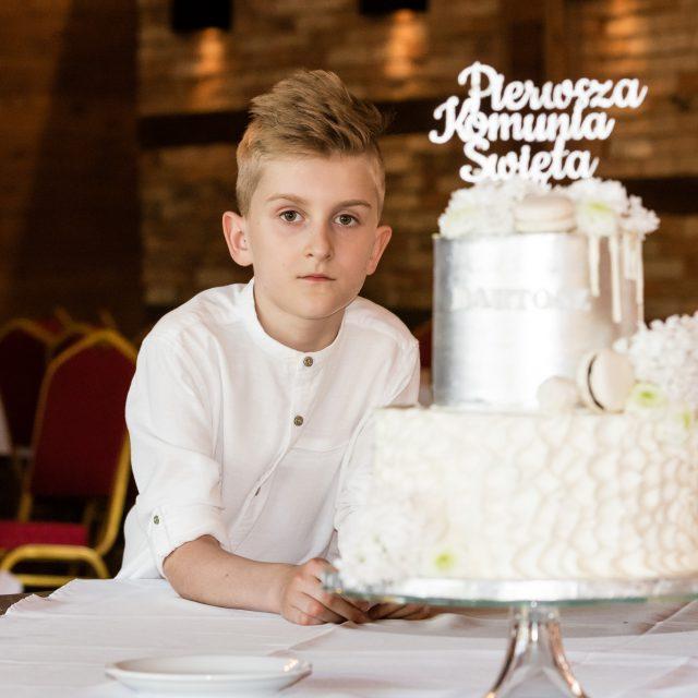 fotografia komunijna białystok - Chłopczyk podczas swojego przyjęcia komunijnego trzyma na rękach wielki tort