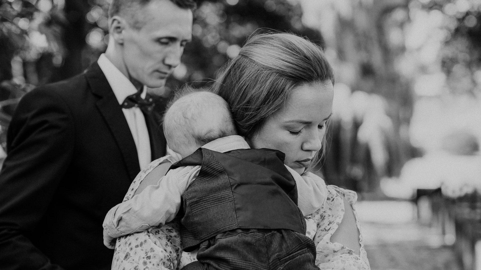 Matka trzymając dziecko na ręku idzie wraz z mężem na chrzest w kościele