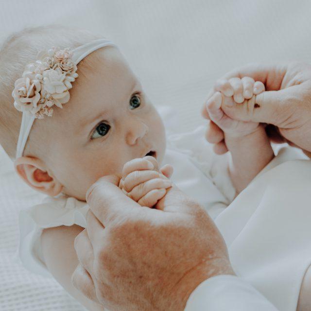 Dziecko ubrane do chrztu łapie za palce swojego ojca chrzestnego
