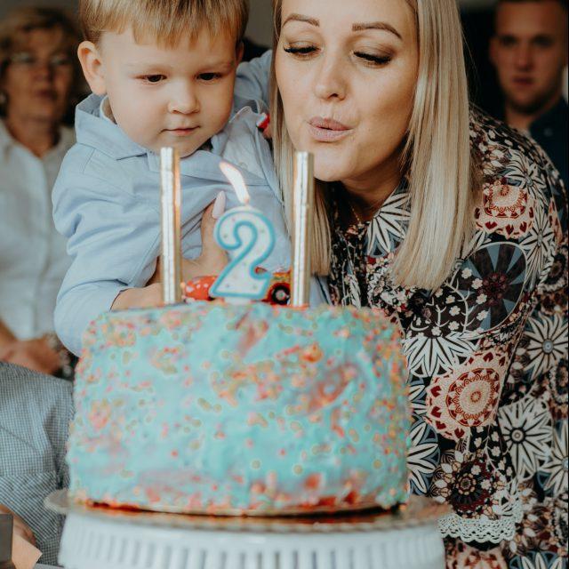 Dwuletni chłopczyk zdmuchuje świeczkę na swoim urodzinowym torcie