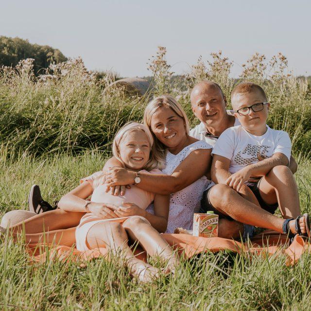 Rodzina siedzi uśmiechnięta na kocu podczas sesji zdjęciowej na łące