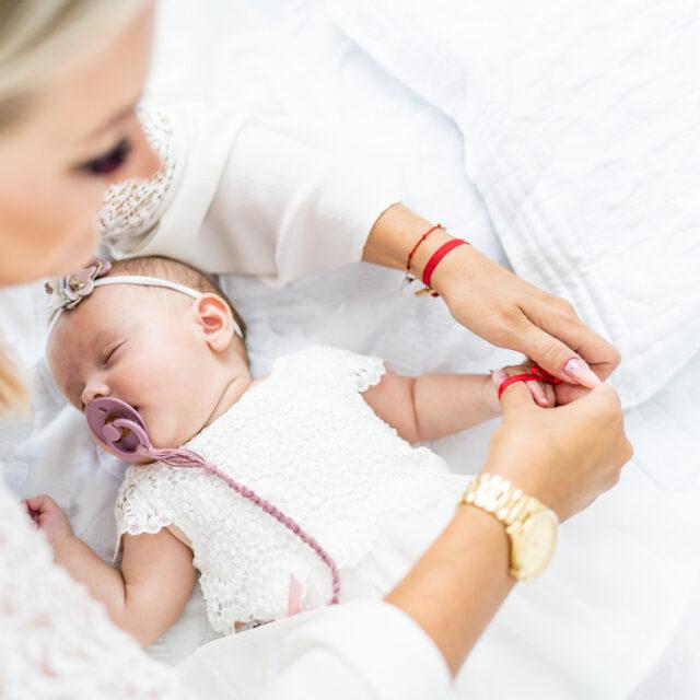 Matka ubiera dziecko do chrztu