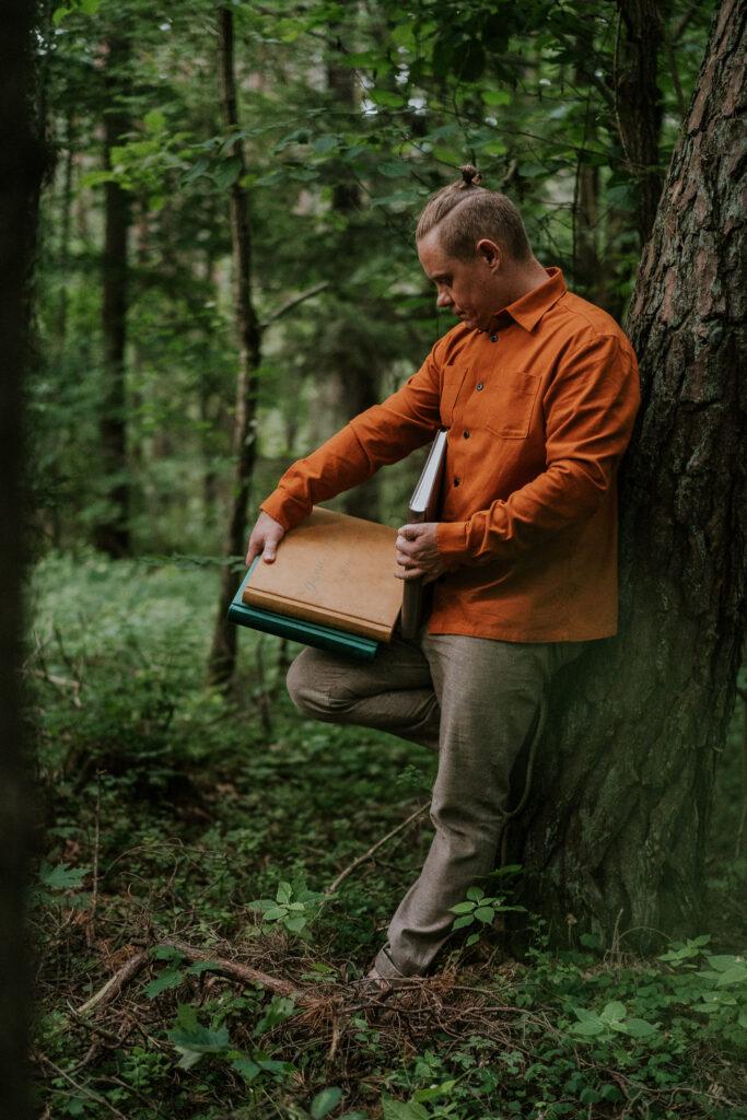 Fotograf Krzysztof Orłowski na zdjęciu z albumami fotograficznymi swoich klientów